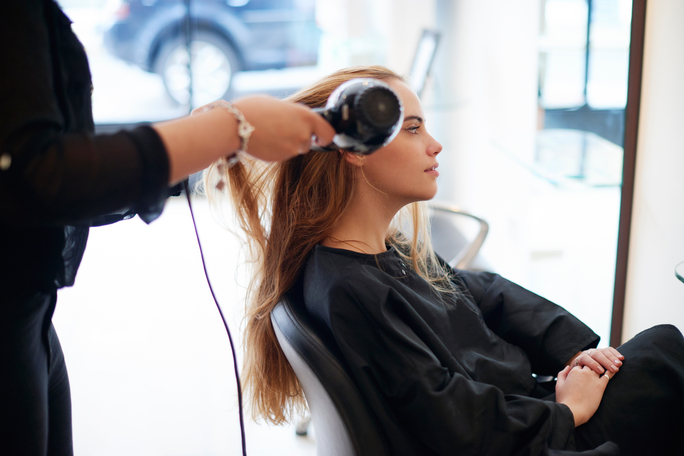 Hairdresser drying customers long hair in salon